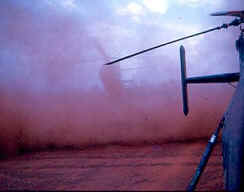 reddish cloud of dust behind helicopter