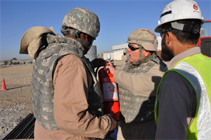 Jeff Ice, a safety and occupational health specialist who deployed to Kandahar from the USACE New York District shows an Afghan construction worker how to detect a fake fire extinguisher. Some counterfeit ones, instead of releasing the normal fire-stopping agent they are supposed to release, spit out flour or other non-effective substances.