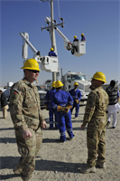 Staff Sgt. Daniel McKinney (left) and Staff Sgt. Troy Madden assess the ongoing training of Afghan electrical engineers and linemen during utility truck training held in early December in Helmand province, Afghanistan. McKinney and Madden are assigned to the U.S. Army Corps of Engineers Prime Power Battalion in Kandahar, Afghanistan.