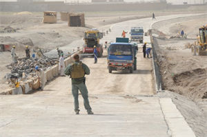 AFGHANISTAN — A GLOBAL employee keeps watch at a bridge bypass construction project. When U.S. Army Corps of Engineers personnel travel to project sites, they are accompanied by a personal security detachment, generally comprised of contractors and military personnel.
