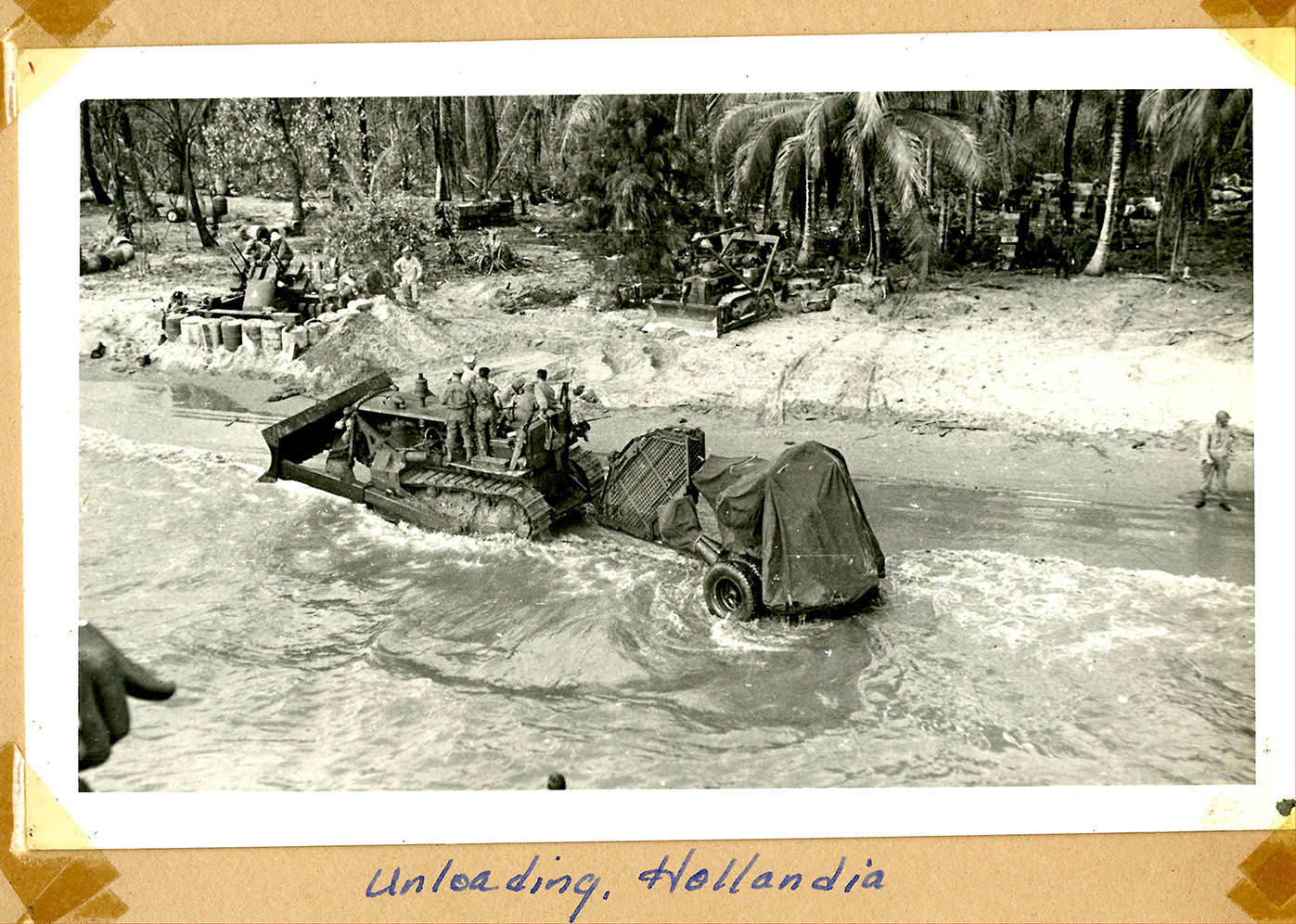 overhead view of men on a bulldozer in shallow water