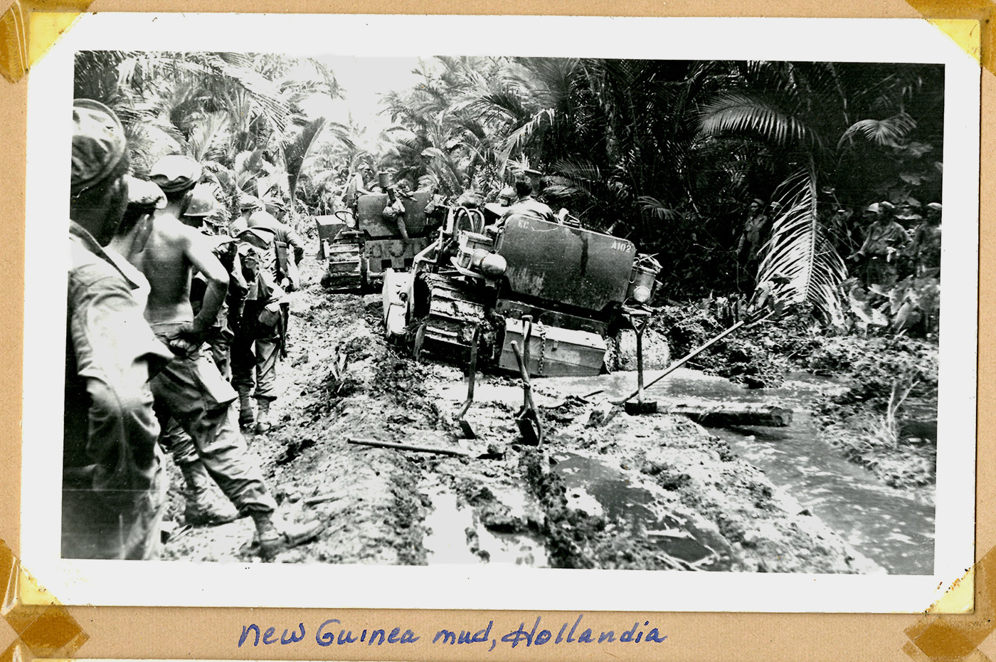 soldiers watch heavy equipment stuck in the mud in a jungle