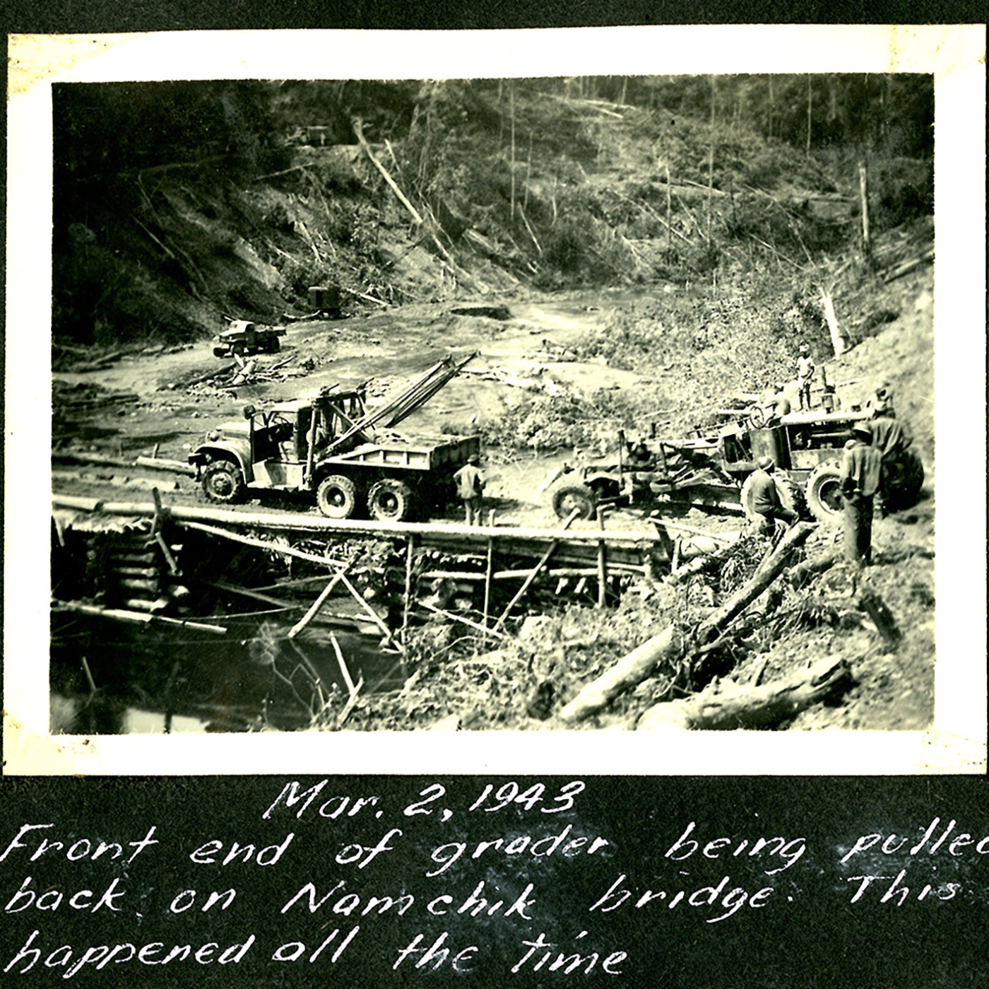 heavy equipment crossing a crude bridge