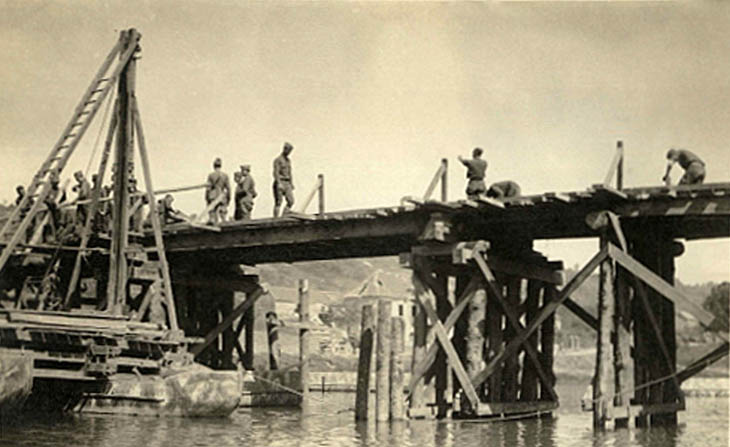 Army engineers building a wooden bridge