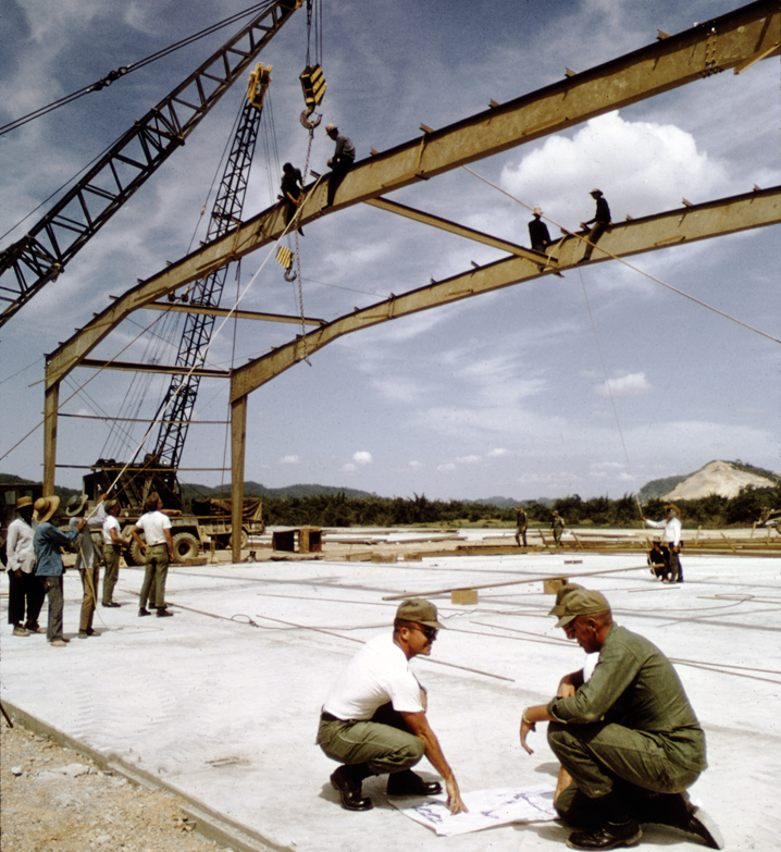 Soldiers on girders of a warehouse under construction