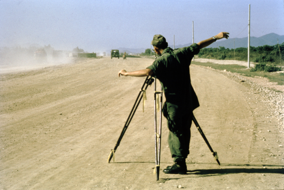 Army engineer with survey equipment on dusty road