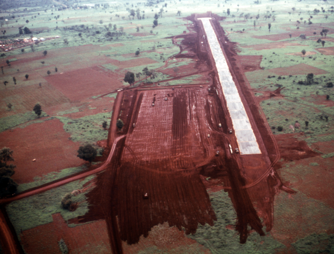 Aerial view of runway in red dirt and green fields