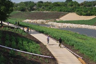 Summer visitors enjoy walking and biking along the completed pathways. When completed the Mission Reach Ecosystem Restoration and Recreation Project will be eight miles in length, restoring the previously channelized San Antonio River closer to its original state, while maintaining its role as a flood risk management area. (Photo by Edward Rivera)