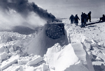 Machinery blowing snow and digging a tunnel